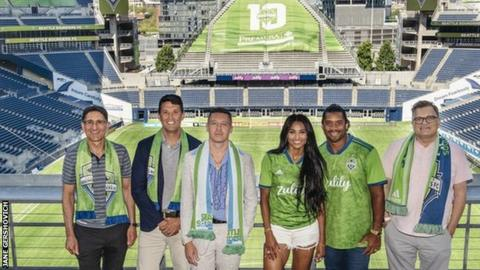 Adrian Hanauer (far left) and Drew Carey (far right) with the new Ownership Group additions, led by (L to R) Terry Myerson, Macklemore, Ciara and Russell Wilson