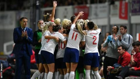 England women celebrate after beating Wales