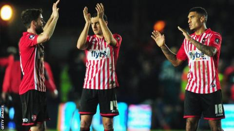 Exeter City players celebrate against Liverpool