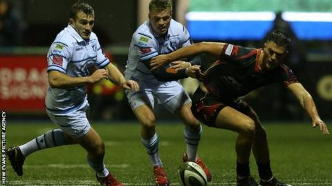 Garyn Smith and Gareth Anscombe of Cardiff Blues go for the ball with Dragons' Jared Rosser
