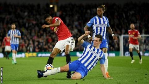 Marcus Rashford is tackled by Lewis Dunk