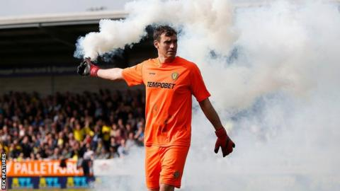 Burton goalkeeper Stephen Bywater clears a smoke bomb from the pitch at the Pirelli Stadium