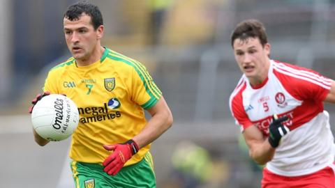 Frank McGlynn of Donegal makes a break with Derry's Kevin Johnston in pursuit