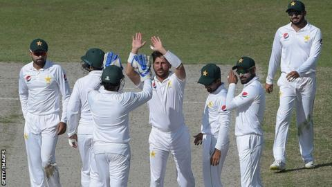 Pakistan leg-spinner Yasir Shah high-fives a team-mate in celebration after taking a wicket in the second Test against New Zealand