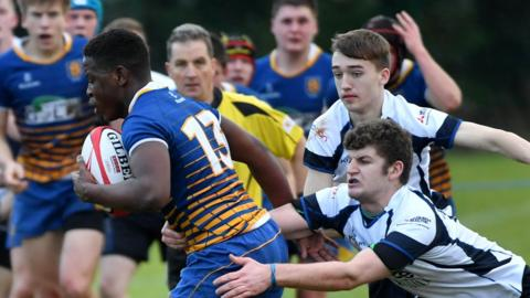 Christopher McKee attempts to halt the progress of Belfast High's Thabisso Madlala during the match which Limavady won 20-16