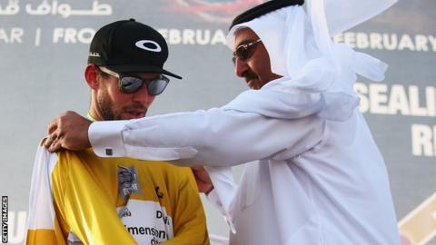 Mark Cavendish is presented with the race leader's jersey