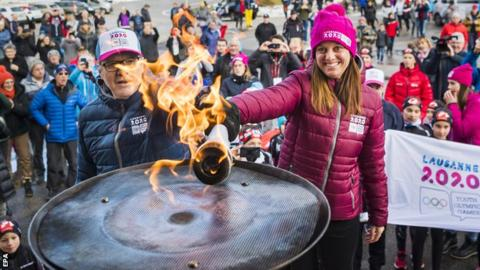 Lausanne 2020 president Virginie Faivre, right, lights the Olympic flame ahead of the Winter Youth Olympics