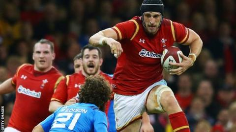 Luke Charteris leaps over a defender while playing for Wales against Italy