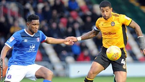 Joss Labadie attempts to control the bouncing ball for Newport as Carlisle's Kelvin Etuhu closes in