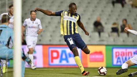 Olympic champion Usain Bolt takes a shot on goal while playing football for Central Coast Mariners