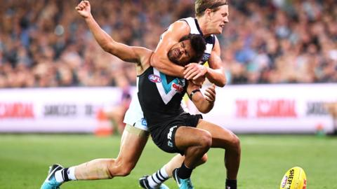 Jake Neade of Port Adelaide is tackled high by Rhys Stanley