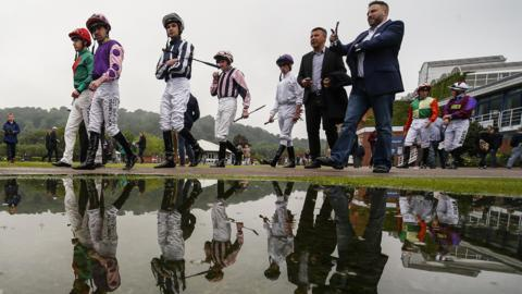 Jockeys make their way to the parade ring at Nottingham Racecourse