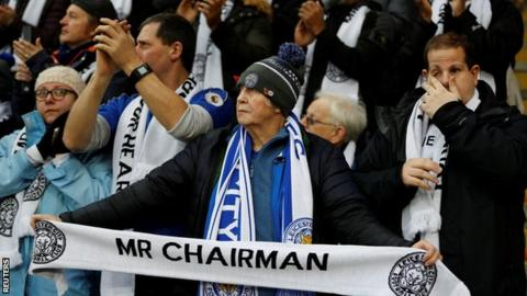 A Leicester fan holding a tribute scarf at the team's first home game since Vichai Srivaddhanaprabha's death.