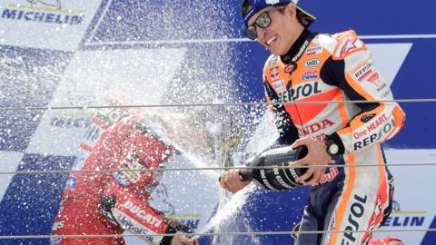 TOPSHOT - Second placed Mission Winnow Ducati's Italian rider Andrea Dovizioso (L) and winner Repsol Honda Team's Spanish rider Marc Marquez spray champagne as they celebrate on the podium at the end of the MotoGP race of the Moto Grand Prix of Aragon at the Motorland circuit in Alcaniz on September 22, 2019. (Photo by JAVIER SORIANO / AFP) (Photo credit should read JAVIER SORIANO/AFP/Getty Images)