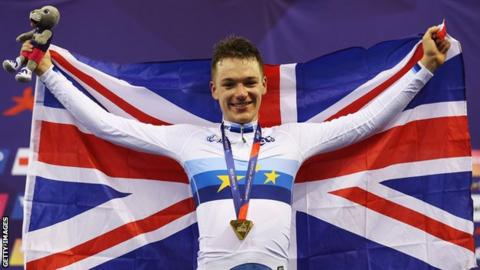 Britain's Ethan Hayter holds up the Union Jack as he celebrates on the podium after winning omnium gold at the 2018 European Championship