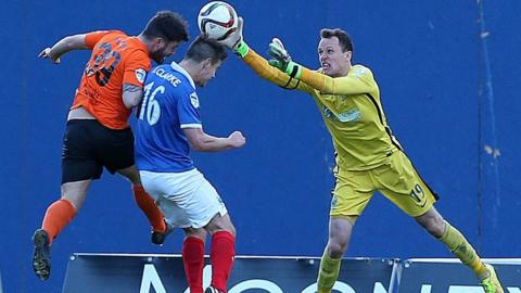 Glenn Taggart and Matthew Clarke challenge for the ball as Linfield goalkeeper Ross Glendinning attempts to clear