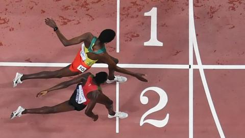 Kenya's Conselsius Kipruto crosses the finish line and wins next to second-placed Ethiopia's Lamecha Girma