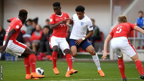 England's Xavier Amaechi is tackled by Swiss goalscorer Felix Mambimbi