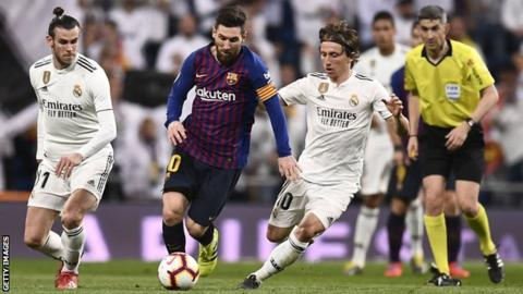 Real Madrid players Gareth Bale (left) and Luka Modric (right) try to get the ball off Barcelona's Lionel Messi (centre) during an El Clasico match