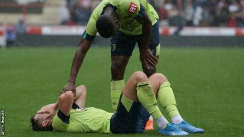 David Brooks is comforted by a team mate after injuring his ankle