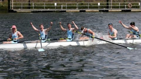 The mens eight from the University of Edinburgh celebrate beating their Glasgow rivals