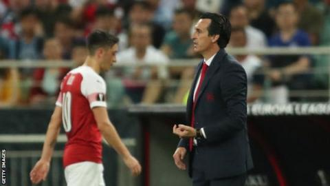 Mesut Ozil walks off the pitch past Arsenal manager Unai Emery