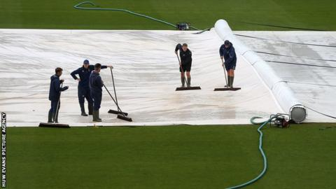 The staff at Glamorgan try and work on the pitch before the match with Surrey was abandoned