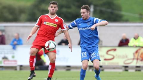 Cliftonville goalscorer David McDaid challenges for possession with Ballinamallard's Colm McLaughlin