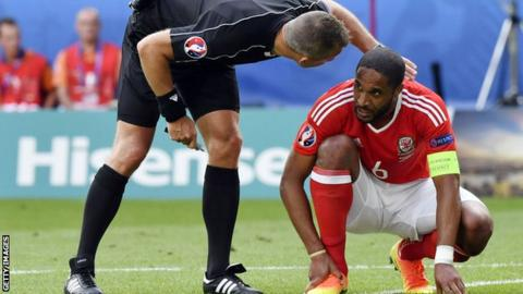 Ashley Williams is injured playing for Wales against Slovakia at Euro 2016