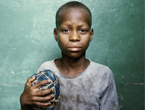 Mozambique: A boy holds a football he has made from tree bark held together with rope. The photo from 'Women Behind the Football Lens,' is part of 'The Game', an exhibition at the National Football Museum, showcasing football cultures around the world.