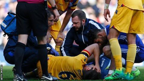 Scott Dann lies injured at Stamford Bridge