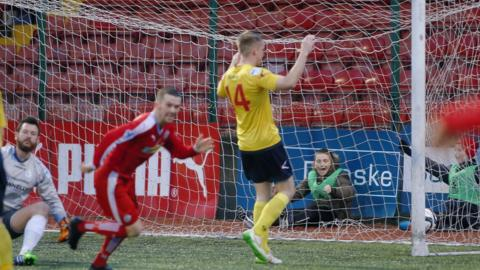 Cliftonville winger Martin Donnelly scores the only goal in the win over Dungannon which moves the Reds to within five points of leaders Crusaders