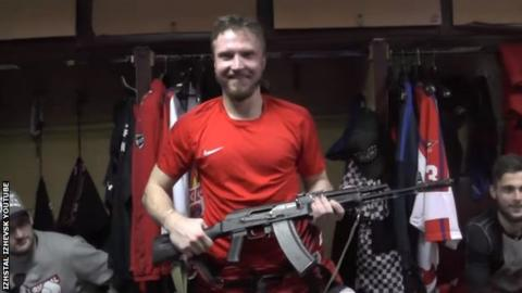 Goalkeeper Savely Kononov poses with the AK47 he was awarded