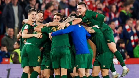 Athletic Bilbao players in a celebratory group huddle