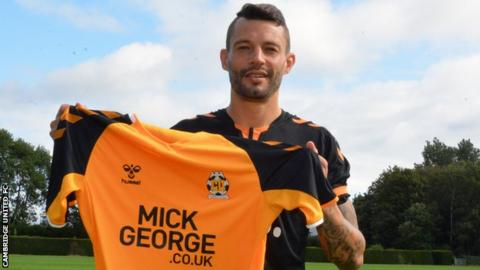 Marc Richards poses with a Cambridge United shirt
