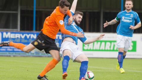 Mark Surgenor puts in a strong challenge on Dungannon's Cormac Burke during Carrick's 2-1 win