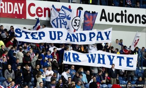 Rangers fans hold up banners which says 'Step up and pay Mr Whyte'
