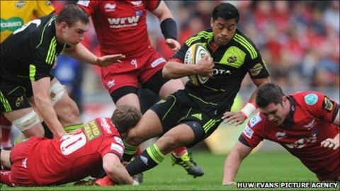 Munster's Lifemi Mafi is tackled by Scarlets fly-half Rhys Priestland