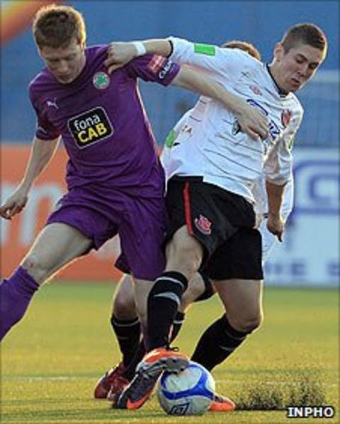 Stephen Garrett of Cliftonville battles for the ball against Daniel Kearns of Dundalk