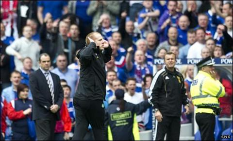 Celtic manager Neil Lennon signals to the Rangers fans
