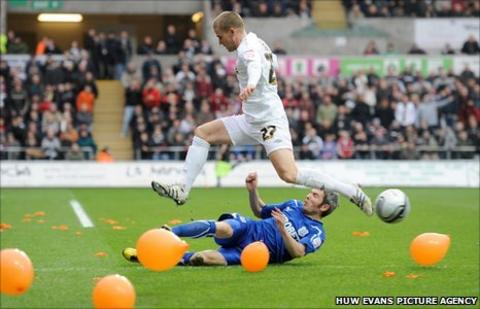 Kevin McNaughton tackles Swansea's Mark Gower