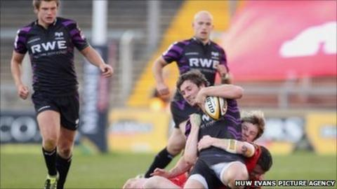 Ospreys centre Andrew Bishop is pulled down by the Munster defence as Dan Biggar (left) and Richard Fussell look on