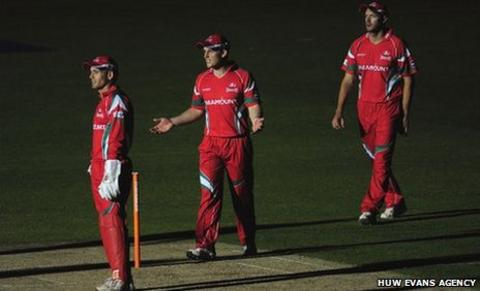 Glamorgan players wait in the dark for play to restart