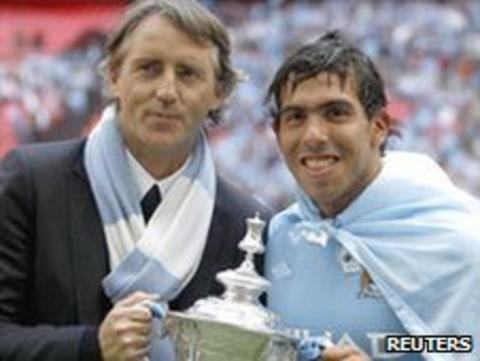 Manchester City boss Roberto Mancini and a striker Carlos Tevez celebrate winning last season's FA Cup