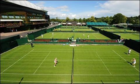 Competitors warm up on Wimbledon's grass during a sunny spell