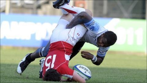 Wales full-back Ross Jones is upended by Fiji's Solomoni Rosolea