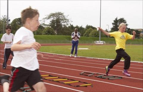 Kriss Akabusi coaches the young athletes