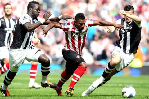 Stephane Sessegnon with two Newcastle United challengers