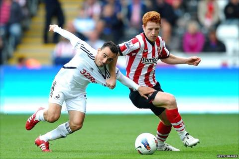 Swansea's Leon Britton tussles with Sunderland's Jack Colback