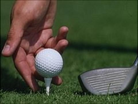 Man putting a golf ball on a tee and a golf club